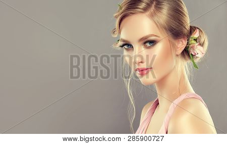 Beautiful Model Girl With Elegant Hairstyle And Rose Flowers In A Braid . Woman With Fashion Spring
