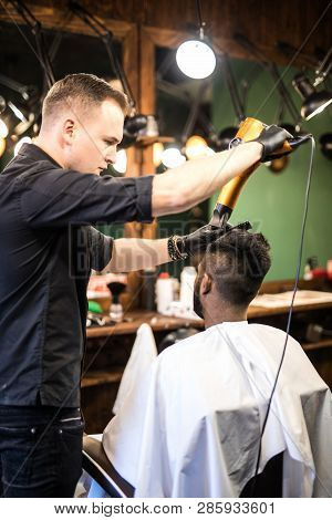 Barber with hairdryer drying and styling hair of client. Barber with hairdryer works on hairstyle for bearded man, barbershop background. Hipster bearded client getting hairstyle. poster