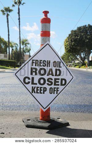 street repair. Fresh slurry or blacktop on surface streets. road work filling pot holes and cracks. fresh oil.