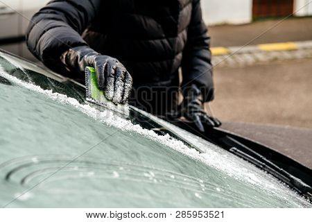 Woman Cleaning Car Windshield From Frost Using Specialized Ice Frost Scraper And Rubber Squeegee Car