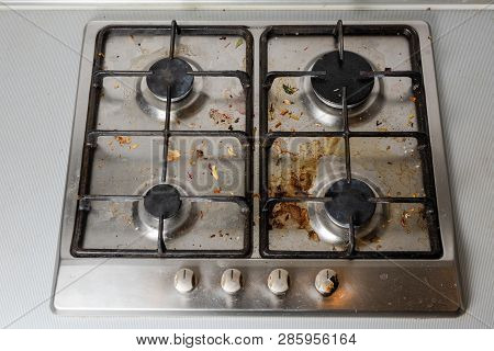 Dirty Gas Stove In The Kitchen, Top View. Gas Stove With Food Remnants.