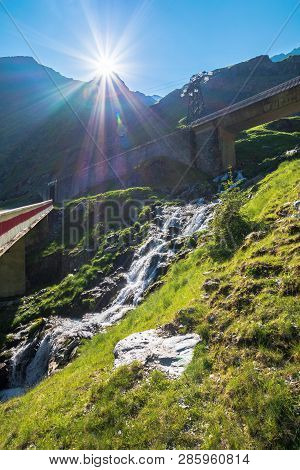 cascades of balea stream in fagaras mountains. road bridge above the grassy meadows. rocky formations in sunlight. beautiful summer scenery