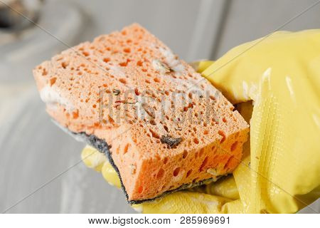 Close-up Of Hand In A Yellow Glove With Dirty Orange Sponge.