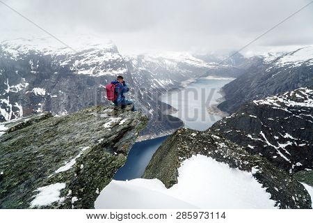 Trolltunga Cliff Under Snow In Norway. Scenic Landscape. Man Traveller Sitting On Edge Of Rock And M