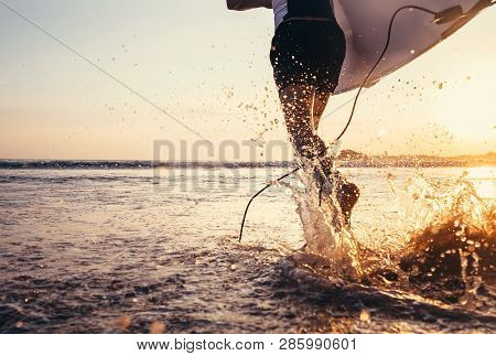 Young Man Surfer Taking Surfboard And Running With Long Surf Board To Waves On The Evening Sunset Sk