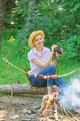 Observing nature concept. Girl ornithology expedition in forest. Girl enjoy hike in forest observing nature. Her hobby is ornithology. Woman tourist holds binoculars while sits on log near bonfire poster