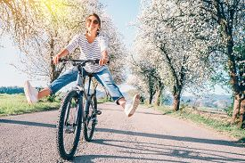 Happy Smiling Woman Cheerfully Spreads Legs On Bicycle On The Country Road Under Blossom Trees. Spri