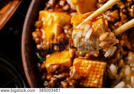 Traditional Chinese Food Mapo Tofu Dish With Pork And Steamed Rice Being Held In Chopsticks