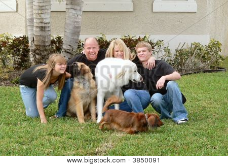 Attractive and happy family with their dogs on a lawn poster