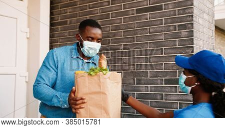 Rear African American Female Courier In Medical Mask Delivering Bag With Healthy Food To Male Client