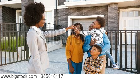 Female Real-estate Selling House To African American Happy Family With Kids. Handing Keys. Outdoors.