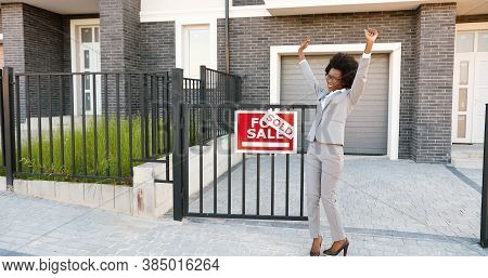 Happy Young African American Beautiful Female Real-estate Agent Dancing And Having Fun At Suburb Str