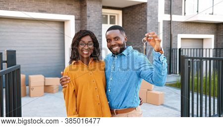 Portrait Of Happy Young African American Man And Woman Smiling To Camera And Demonstrating Key Of Ne