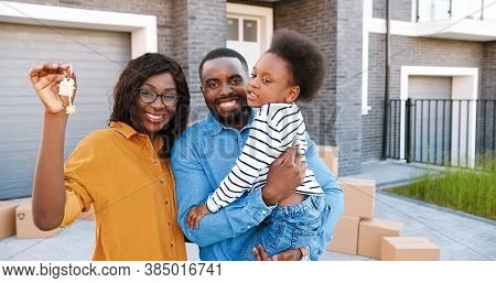 Portrait Of Happy African American Family With Small Cute Girl On Hands Standing At Big House On Sub