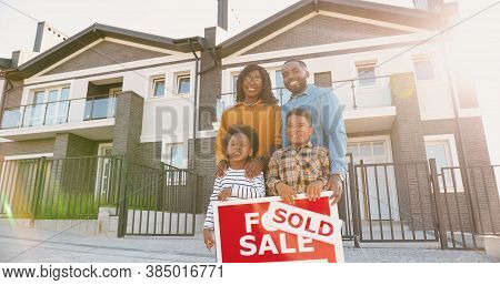 Portrait Of Happy African American Family With Small Children Standing At New House At Suburb And Sm