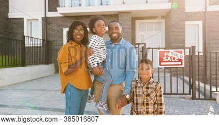 Portrait Shot Of Happy African American Family With Small Children Standing At New House At Suburb A