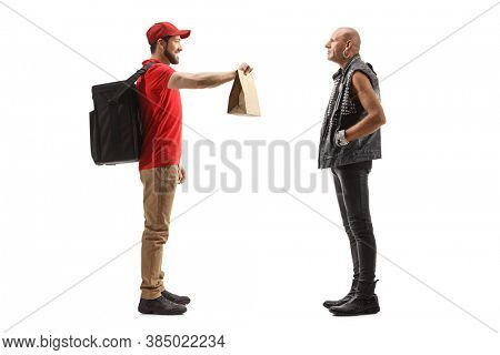 Full length profile shot of a guy delivering food bag to a punk rocker isolated on white background