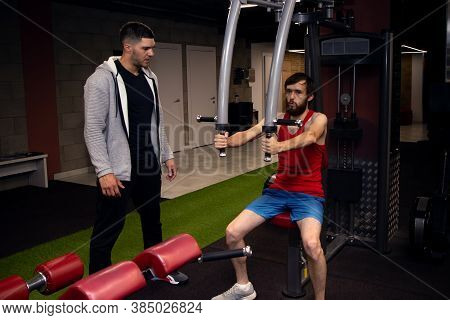Fitness Young Man With Sportswear Exercising His Pectoral On Butterfly Weight Machine. Using Trainin