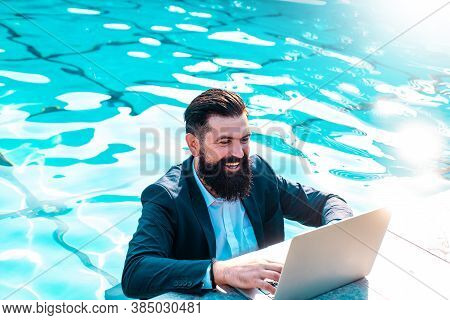Happy Businessman In Suit With Laptop In Swimming Pool. Funny Business Man Relaxing With Notebook. C