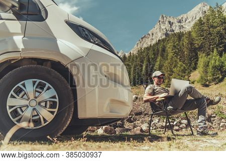 Caucasian Men With Modern Laptop Computer In His Hands Working Remotely While Camping In Rv Camper V