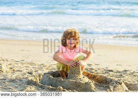 Kid Playing On The Beach On Summer Holidays. Child Building A Sandcastle At Sea. Boy Play With Sand