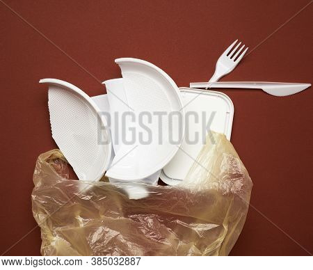 Used Plastic Dishes, Pieces Of Plastic And A White Plastic Bag On A Brown Background, Top View, Flat