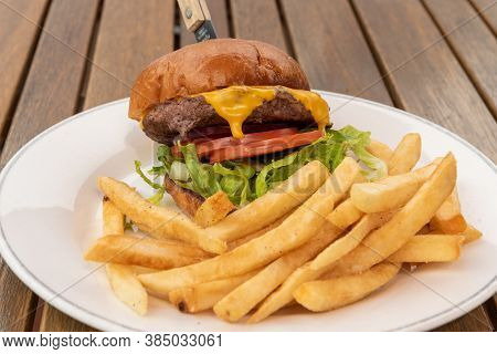 Large And Tall Cheeseburger Topples Over From The Weight Of Large Patty, Melted Cheese, Sliced Tomat