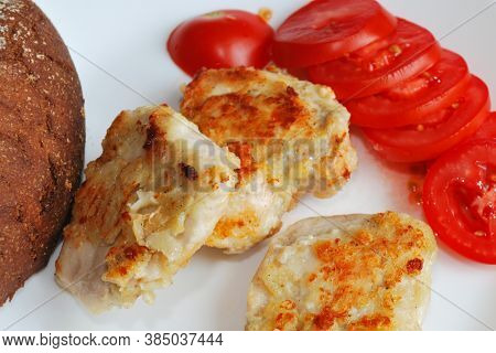 Fried Sliced Chicken Fillet With Sliced Tomato In White Surface.