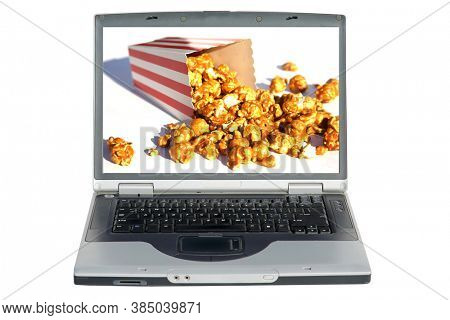 Laptop Computer. Laptop Computer with a  spilled box of Caramel Popcorn. Caramel Popcorn is enjoyed world wide. Isolated on white. Room for text.