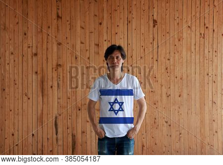 Man Wearing Israel Flag Color Shirt And Standing With Two Hands In Pant Pockets On The Wooden Wall B