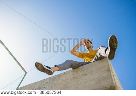 Man Sitting On A Ledge Looking Around