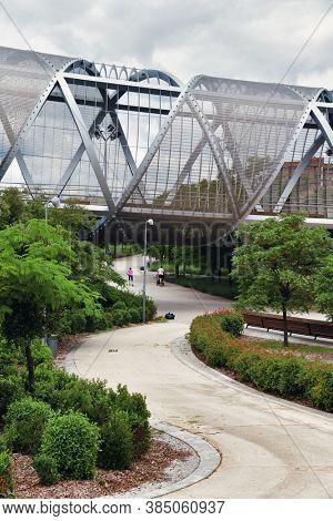 MADRID, SPAIN – MAY 13, 2018: Arganzuela Footbridge, designed by Dominique Perrault, is a modern pedestrian bridge located in Arganzuela Park.