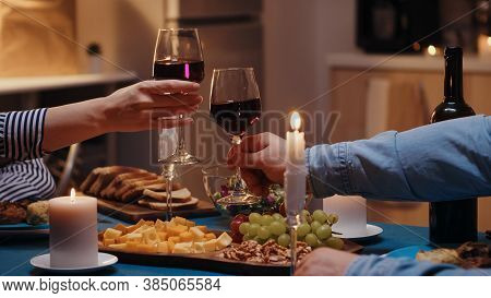 Close Up Of Clinking Red Wine Glasses During Romantic Dinner. Happy Cheerful Young Couple Dining Tog