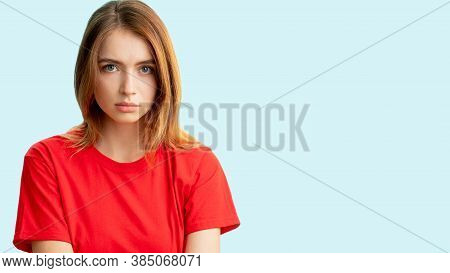 Worried Woman Portrait. Female Rights. Disturbed Insecure Lady In Red T-shirt Looking At Camera Isol
