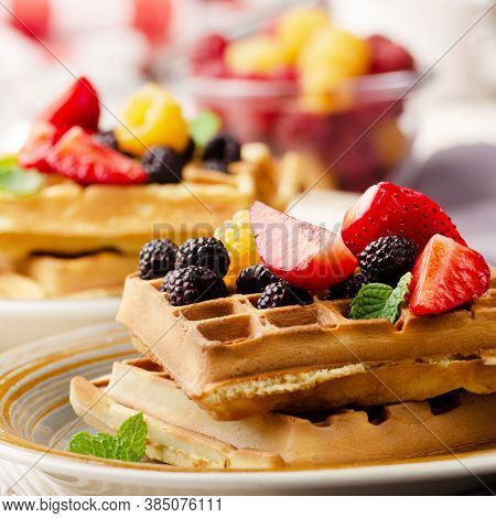 Closeup View At Belgian Waffles Served With Strawberries And Blackberries On Kitchen Table