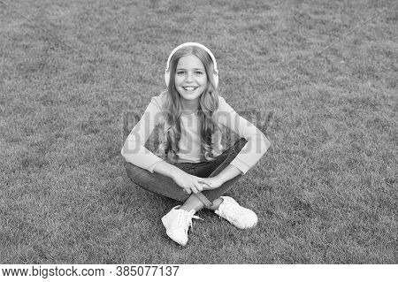 Relax On Green Grass. Spring Leisure Time. Happy Childhood. Kid In Headset. Happy Little Girl Listen