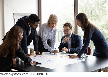 Diverse Colleagues Brainstorm Discuss Paperwork At Meeting