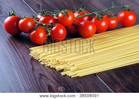 spaghetti and tomatoes on a wooden table