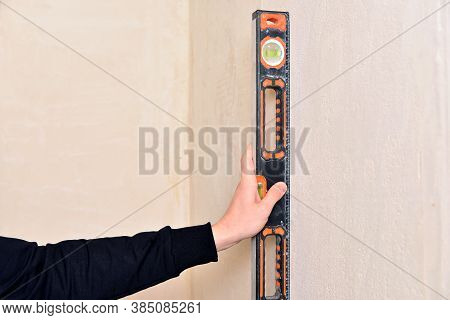 Worker Hand Holds Spirit Level. Check The Inclination Of The Wall With Building Level