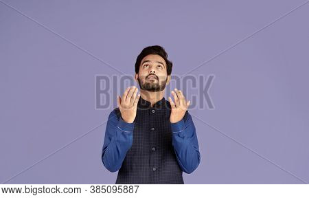 Religious Indian Guy Praying To God, Asking For Redemption On Violet Background, Panorama