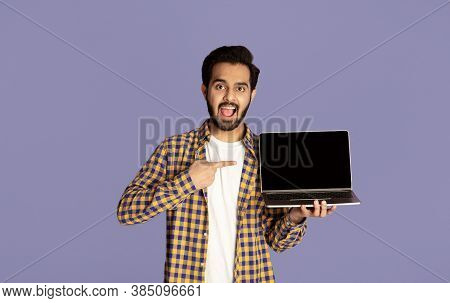 Excited Indian Guy Pointing At Empty Laptop Screen Over Violet Background, Mockup For Website Design