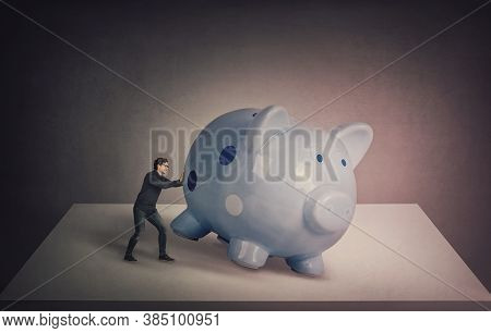 Surreal Business Concept, Tiny Businessman Trying To Push A Huge Piggybank Out Of The Table, To Get