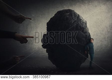 Scared Businessman Hiding Behind A Huge Boulder, Feels Discomfort As People Hands Pointing To Him Bl