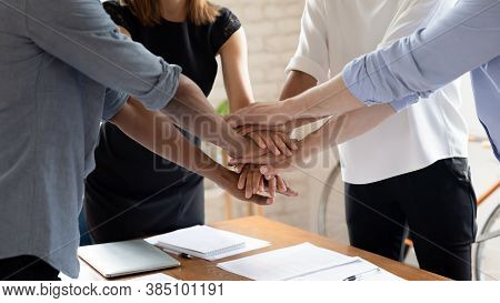 Diverse Colleagues Stack Hands Engaged In Teambuilding Activity