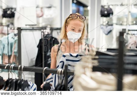 Fashionable Woman Wearing Protective Face Mask Shopping Clothes In Reopen Retail Shopping Store. New