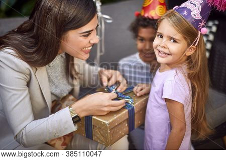 beautiful young adult female unwrapping birthday present for little caucasian girl looking at camera, smiling