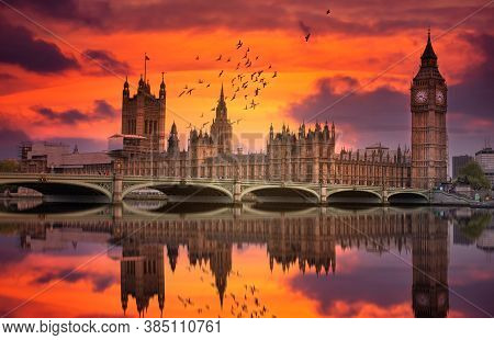 London Westminster And Big Ben Reflected On The Thames At Sunset With Birds Flying Over The City