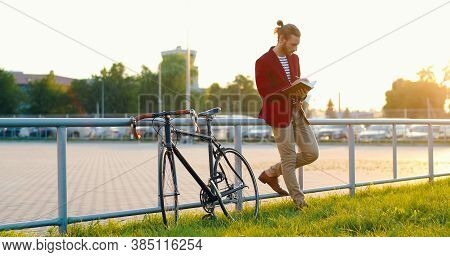 Caucasian Stylish Male Bike Rider Standing At Street, Leaning And Writing Plans In Notebook. Handsom