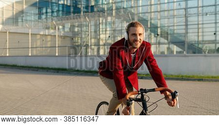 Caucasian Cheerful Young Stylish Male Bicyclist In Red Casual Jacket And Headphones Riding A Bike At