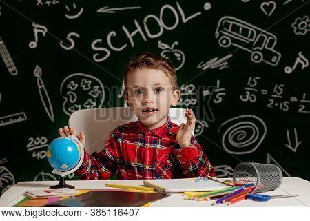 Preschooler Boy Making School Homework. School Boy With Happy Face Expression Near Desk With School